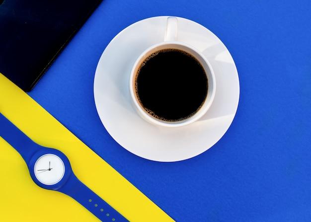 Tasse de café blanche sur fond bleu, montre à main bleue sur fond jaune, carnet noir