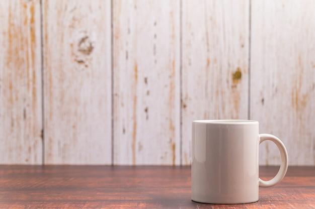 Tasse à café blanche sur fond en bois avec espace de copie