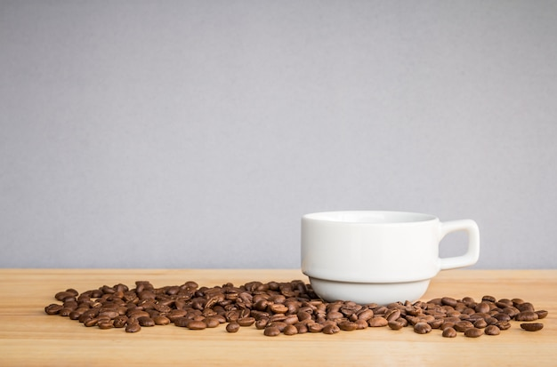 Tasse à café blanche et grains de café sur un bureau en bois avec fond gris