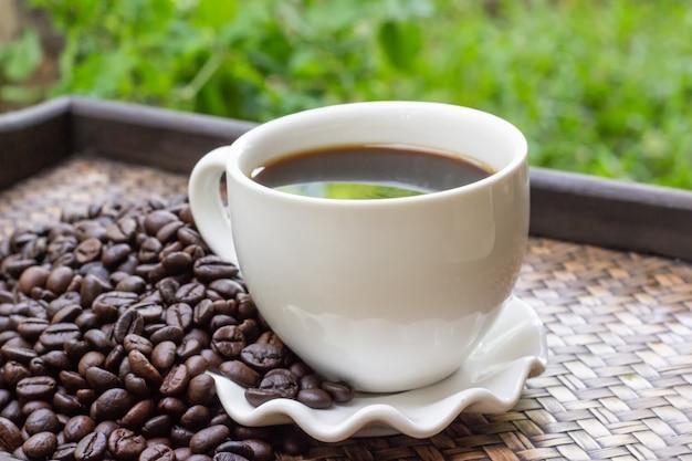 Tasse à café blanche avec grains de café placés sur un plateau.