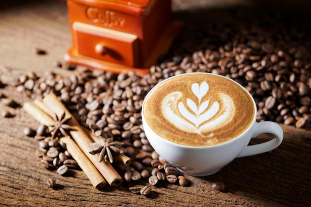 Tasse à café blanche et grains de café torréfiés autour