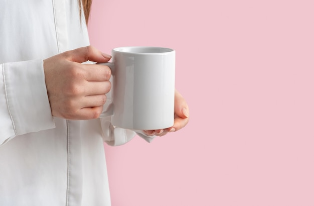 Tasse à café blanche maquette ou mug en mains féminines sur rose