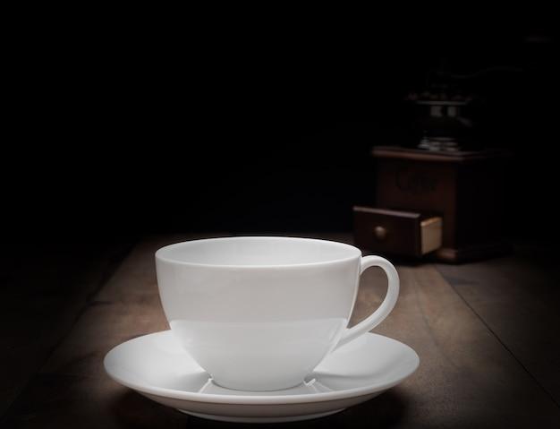 Tasse à café blanche et moulin à café sur fond en bois grunge