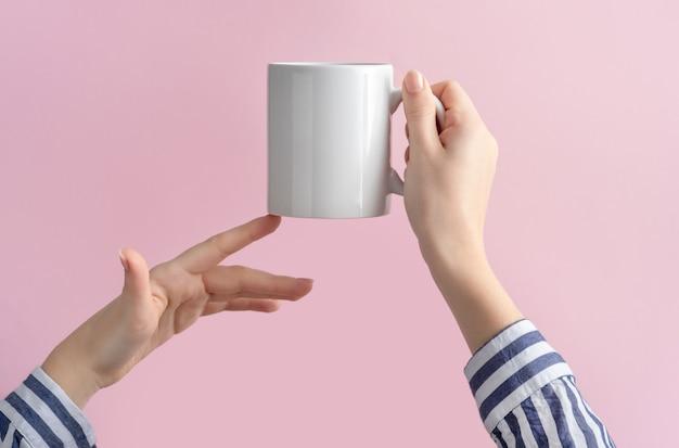 Tasse à café blanche ou mug dans les mains des femmes sur rose