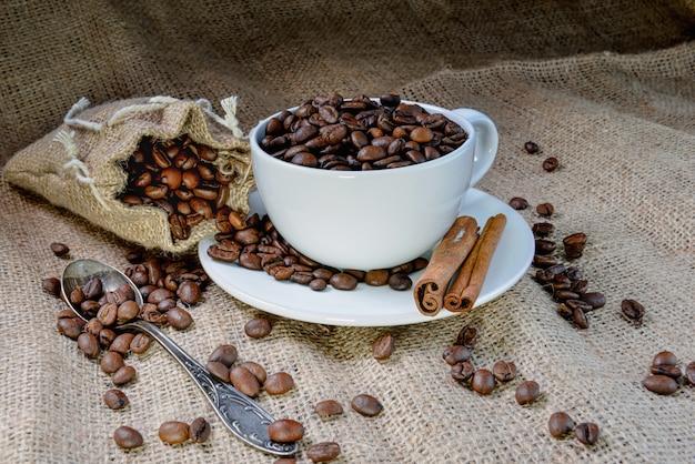 Tasse à café blanche pleine de grains de café bio et de bâtons de cannelle sur toile de lin
