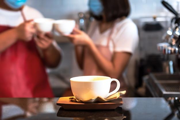 Une tasse de café blanche posée sur le comptoir avec le flou de deux baristas portant un masque de fond