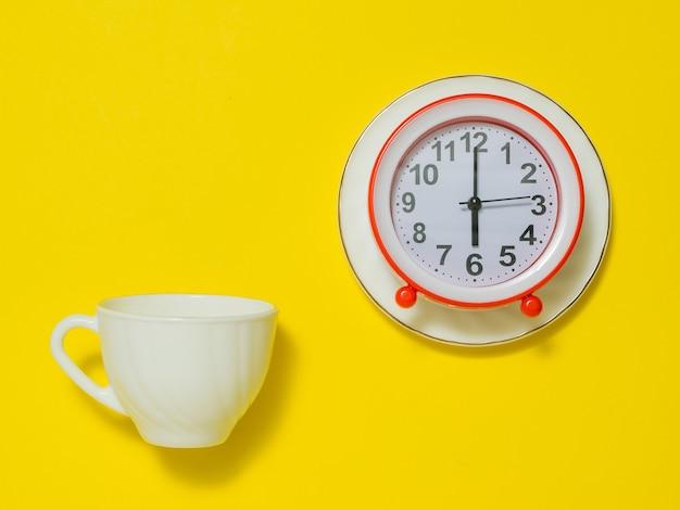 Tasse à café blanche et réveil sur une soucoupe sur fond jaune. le concept de lever le ton le matin. mise à plat.