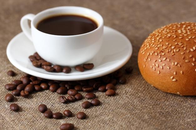 Tasse à café blanche sur soucoupe, pain aux graines de sésame et grains de café épars sur nappe de jute.