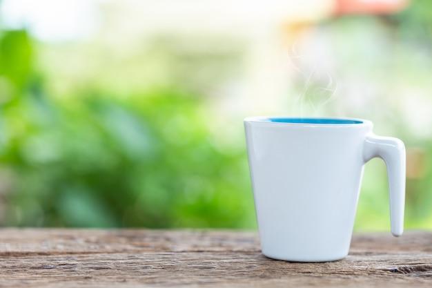 Tasse à café blanche sur une table ou un comptoir en bois dans un café-restaurant et flou fond bokeh léger