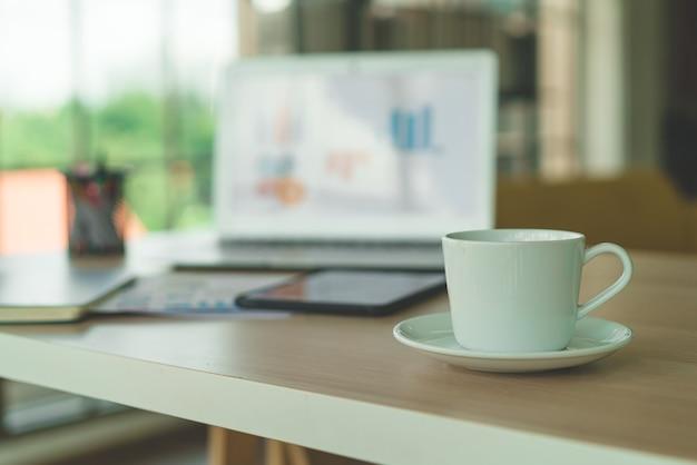 Tasse à café blanche sur table de travail - effet filtre vintage