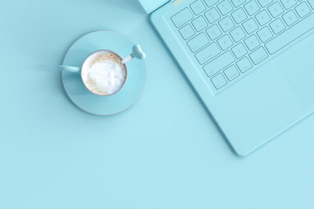 Tasse de café bleu à côté de l'ordinateur portable sur le bureau