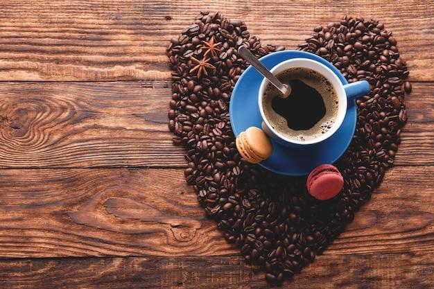 Tasse de café bleu, macarons, haricots en forme de coeur