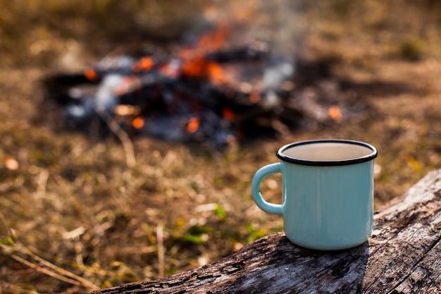 Une tasse de café bleue et un feu de camp brûlé