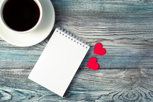 Tasse à café, bloc-notes et deux coeurs sur un fond en bois.