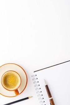 Tasse de café, bloc-notes et stylo sur un fond en bois blanc. vue de dessus du lieu de travail. lieu d'inscription