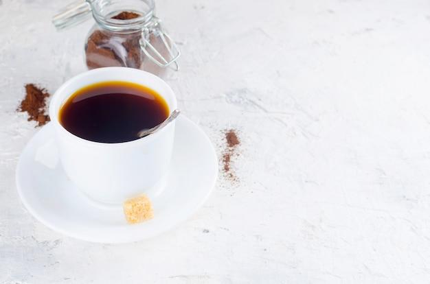 Tasse de café et un bocal en verre avec de la poudre de café