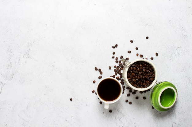 Tasse de café, une boîte de grains de café et de grains de café sont dispersés sur un fond en béton.