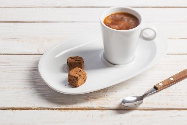 Tasse de café avec des bonbons au chocolat sur une vieille table en bois blanc
