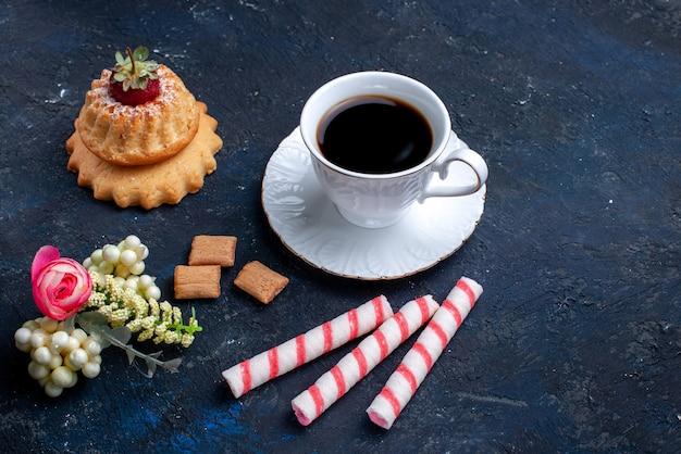 Tasse de café avec des bonbons de bâton rose et délicieux gâteau sur bleu, boisson au café biscuit sucré