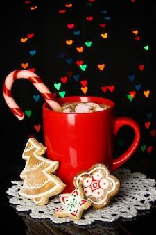 Tasse de café avec des bonbons de noël sur fond de lumières de noël