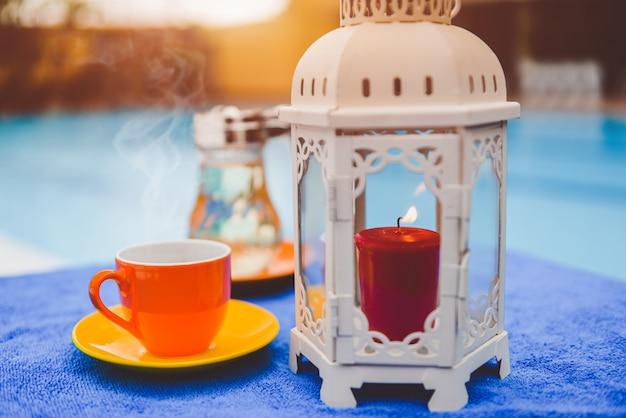 Tasse à café et bougie au bord de la piscine de l'hôtel