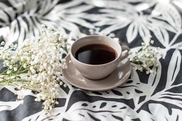 Tasse de café et une bougie sur un plateau de service en bois rustique dans le lit confortable avec couverture.