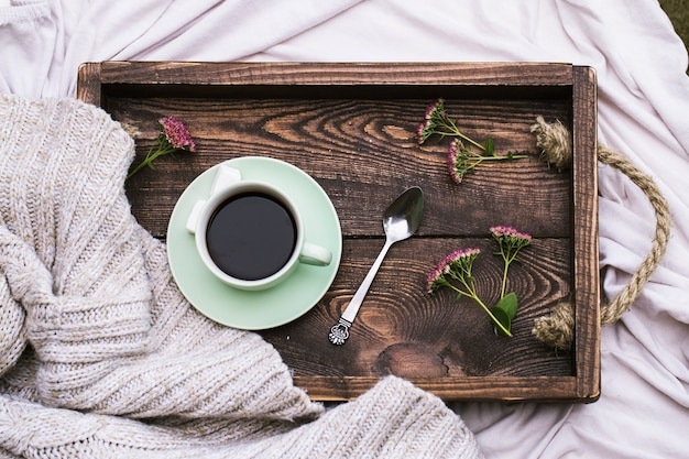 Tasse de café et bougie sur plateau de service en bois rustique et tricoter un pull en laine chaud