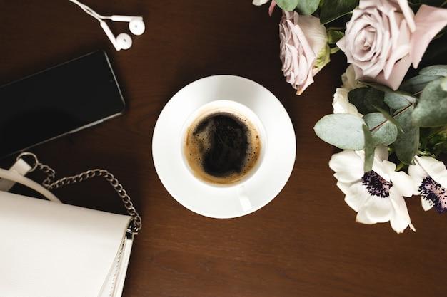 Une tasse de café avec un bouquet d'anémone tendre, de branches d'eucalyptus et de roses violettes pastel, un sac à main, des écouteurs et un téléphone sur une table en bois marron.