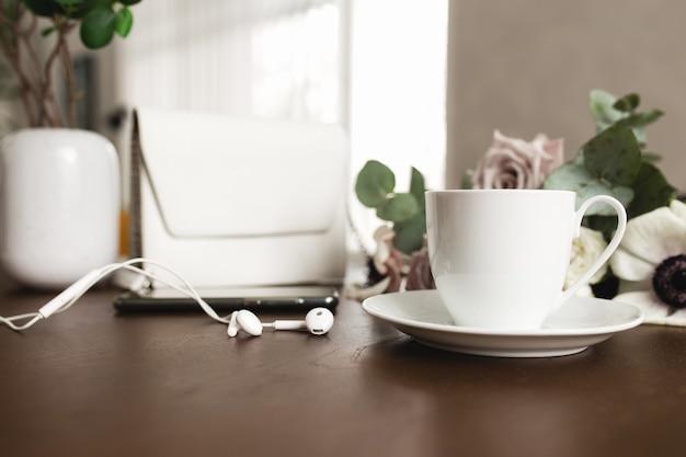 Une Tasse De Café Avec Un Bouquet D'anémone Tendre, De Branches D'eucalyptus Et De Roses Violettes Pastel, Un Sac à Main Femme, Des écouteurs Et Un Téléphone Sur Une Table En Bois Marron. Photo Premium