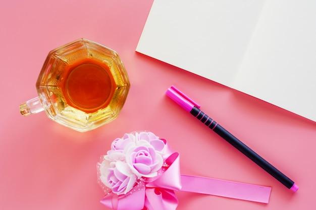 Tasse de café avec bouquet de cahier, stylo et fleur ouvert sur fond rose
