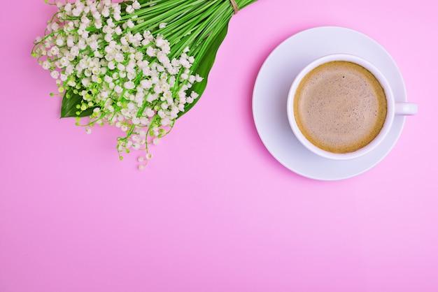 Tasse de café et un bouquet de lis blancs de la vallée