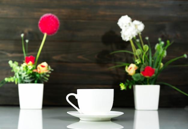 Tasse à café et bouquet de vase de fleurs artificielles sur table