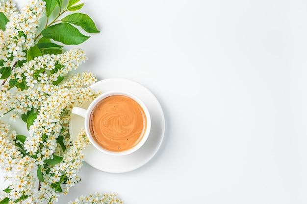 Une tasse de café et une branche avec des fleurs sur fond blanc. vue de dessus, horizontale. espace de copie.