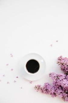Tasse de café et de branche de lilas sur blanc