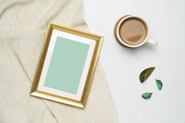 Tasse de café et cadre photo or mock up sur fil marron et fond en bois blanc.