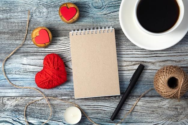 Tasse de café et un cahier, entouré de coeurs et de bougies sur fond en bois.