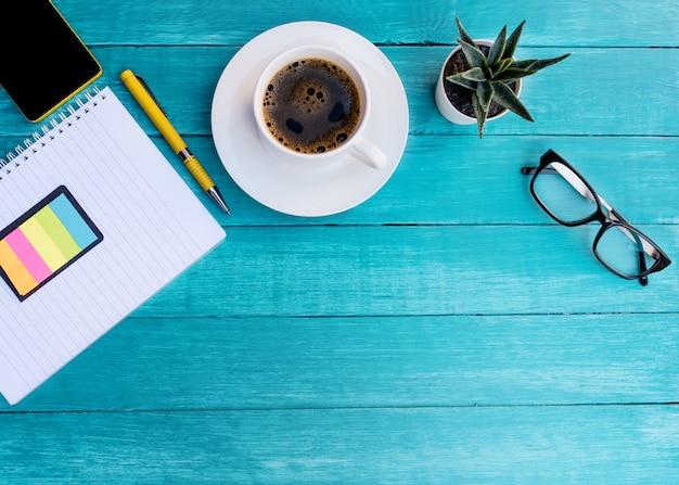 Tasse de café, cahier, plante, verres et téléphone sur un bureau en bois turquoise.
