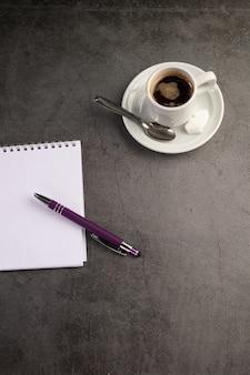 Tasse à café avec un cahier et un stylo
