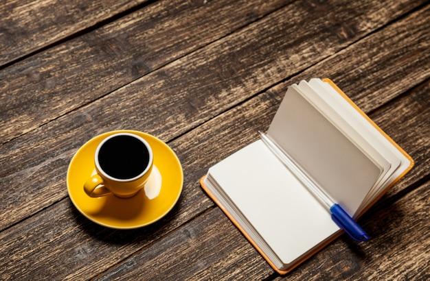 Tasse à café et cahier sur une table.