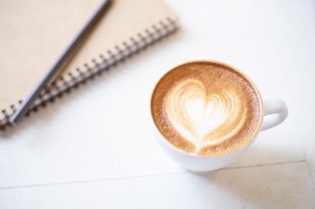 Tasse à café avec cahier sur table