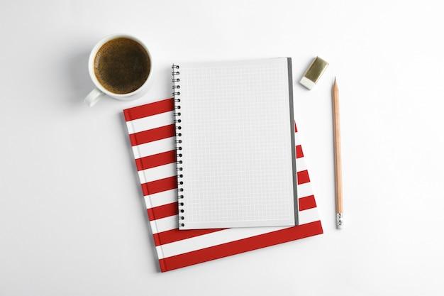 Tasse de café avec cahiers et crayon, vue de dessus