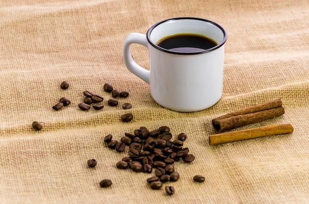 Tasse de café avec cannelle et grains