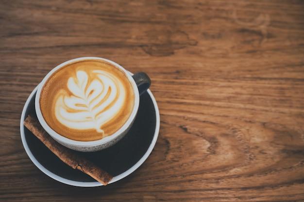 Une tasse de café cappuccino avec arts de la latte sur une table en bois à l'arrière-plan du café avec filtre vintage.