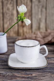 Tasse de café cappuccino blanc et fleur de freesia blanc