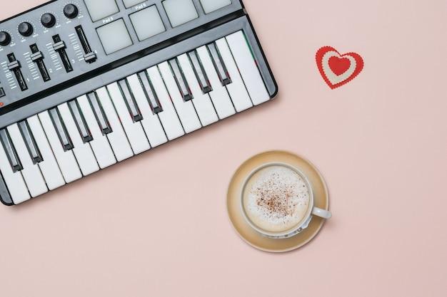 Une tasse de café cappuccino à la cannelle et un mixeur de musique sur une surface rose