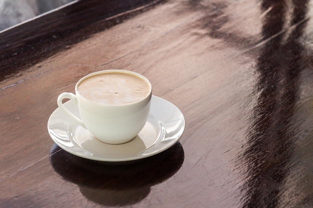 Tasse de café cappuccino chaud sur le pont en bois foncé