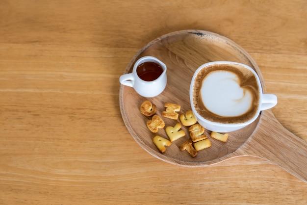 Tasse à café cappuccino avec du sucre sur une assiette en bois et table en bois, vue de dessus