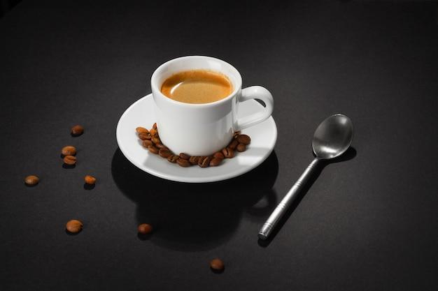 Tasse de café cappuccino sur fond noir dans un cercle de lumière.