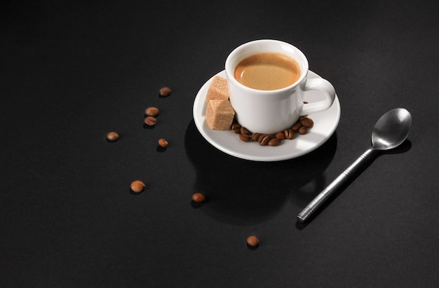 Une tasse de café cappuccino sur fond noir, des grains de café, des morceaux de sucre et une cuillère à café éclairée par une lumière vive.