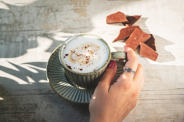 Tasse avec café cappuccino, une main féminine est prise par une tasse.